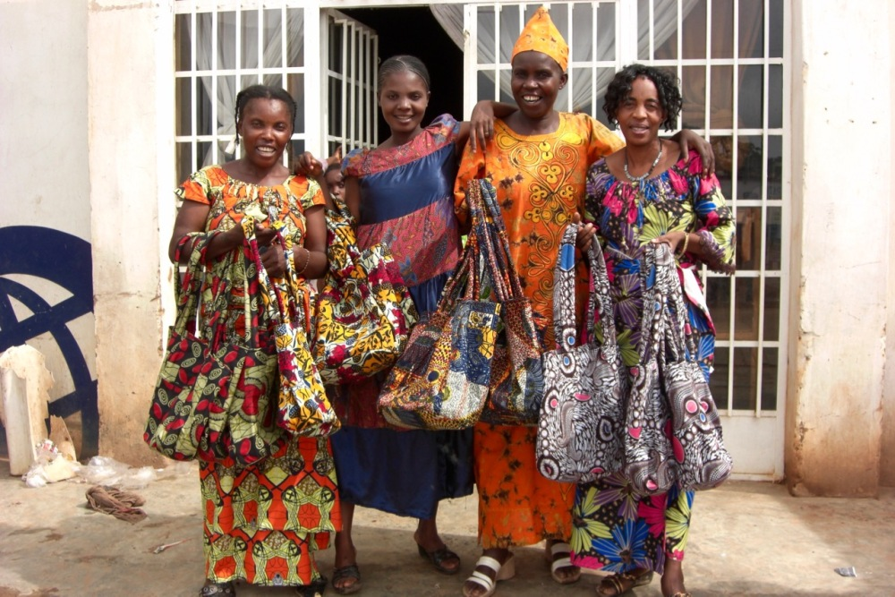 Local tailors presenting their finished product, custom-made shoulder bags. Association Couturière pour la Relance de la Femme Rural, Fungurume, November 2011.